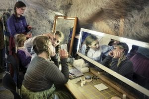 Young girls in old costumes putting on make-up in front of a mirror, preparing themselves for the local play, Klemetspelet.
