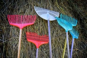 Colorful rakes in blue, purple and red, standing up to a wall of straws as decoration for the outdoor play, Klemetspelet.