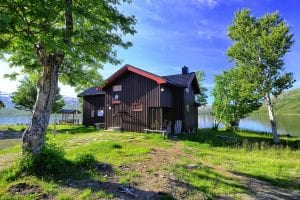 Picture of the cabin, Kjenvasshytta, with the lake right behind it and beautiful mountain surroundings.