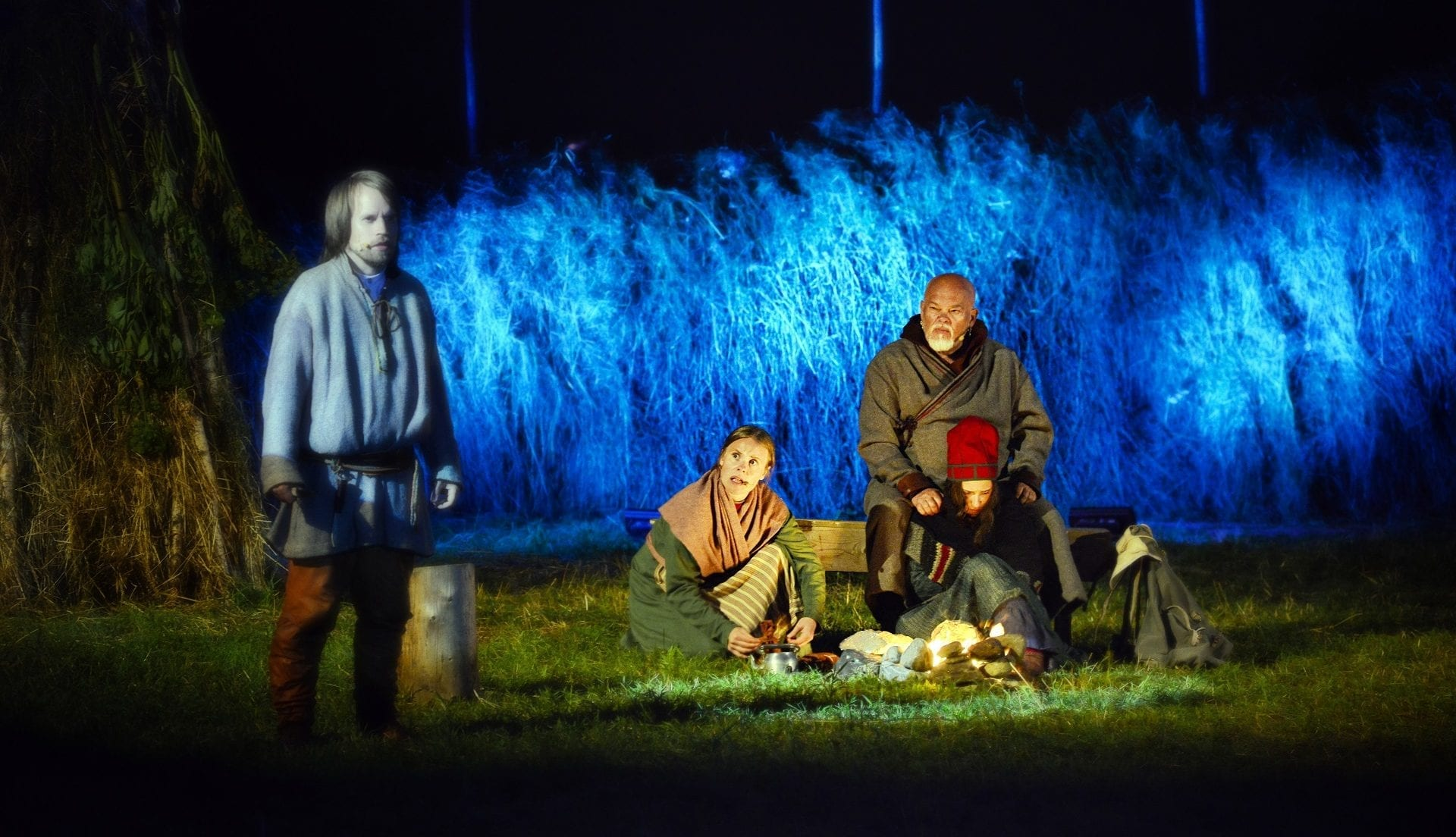 Main characters in old costumes sitting next to an open fire during local play, Klemetspelet, with blue lights behind.