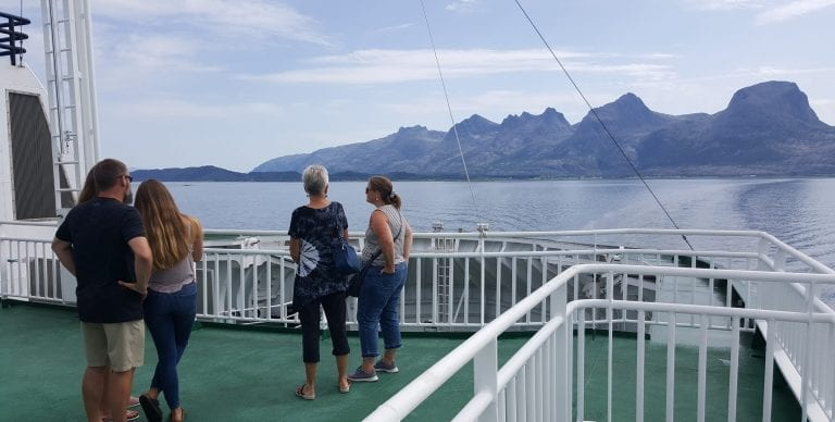 People standing outside on the top of the ferry on a summer day, with a great view of several grand mountains around them.