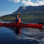 Kayaker at Tustervatnet lake, on a quiet day in great mountain environments.