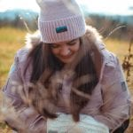 """Smiling woman outside in nature wearing a purple winter hat matching her jacket, and white mittens, both from """"Okstind""""."""