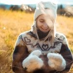 """Smiling woman outside in nature wearing a matching white knitted set from """"Okstind"""" with winter hat and mittens."""
