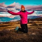 """Colorful woman jumping of joy from being outside in beautiful nature wearing an orange winter hat from """"Okstind""""."""