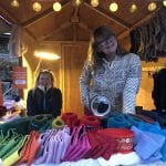 """Happy, smiling """"Okstind""""-ladies at """"Jul på Berget», a Christmas festival, selling their colorfully knitted products."""