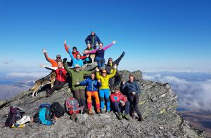 Lots of colorful and happy people celebrating being on top of Oksskolten, Norther-Norway's highest mountain.