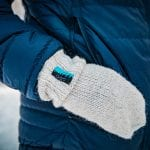 """Knitted white mittens from """"Okstind"""" matching with the blue jacket the model is wearing."""