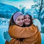 """Two sisters smiling and hugging each other, wearing knitted headbands and mittens from """"Okstind""""."""