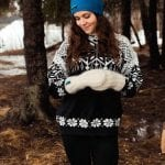 """Smiling woman outside in nature with bright blue knitted headband from """"Okstind""""."""