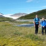 Three young kids with matching blue clothes smiling in beautiful surroundings in the mountain during summer.