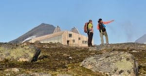 Two colorful hikers standing in front of the designer cabin, Rabothytta, surrounded by magnificent wilderness during summer.