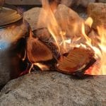 A coffeepot laying on an open, yellow fire that is surrounded by stones.