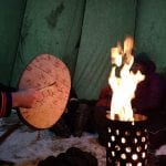 Someone playing on a sami drum covered with sami pictograms in front of a fire inside a lavvo, a sami tent.