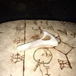Sami drum covered with sami pictograms and a sami-hammer laying on top of the drum ready to be played.