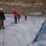 Happy people on top of the glacier having overcome the challenge of climbing the daring glacier cracks.