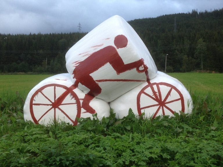 "White silage bales standing on an acre, painted with a red cyclist as decoration for ""Artic Race"" in 2016."