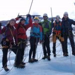 Six happy people equipped with rope, crampons and ice axe on a glacier.