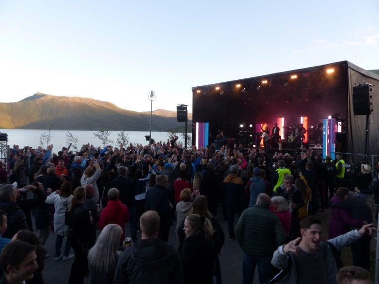 "People dancing in front of the stage at ""Båt of fjord""-festival, located right next to fjord and mountains at Hemnesberget."