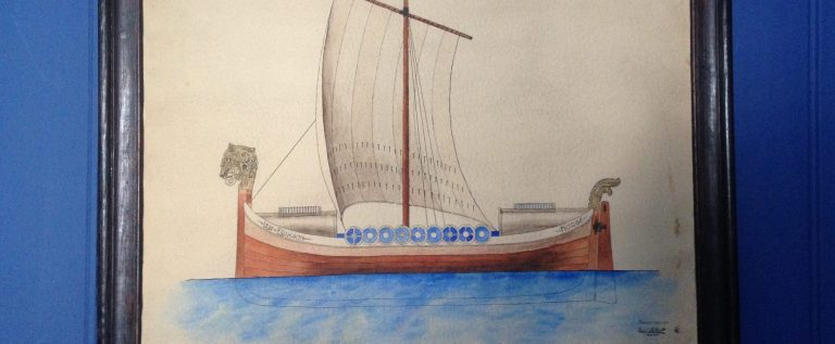 A framed drawing hanging on a blue wall, of a wooden ship with white sails on the blue ocean.