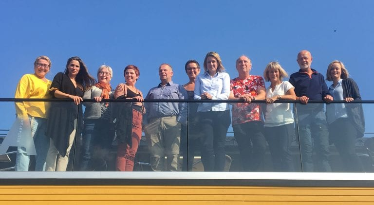 11 smiling partners of the Okstindan Park gathered standing up on a roof veranda in the sun.