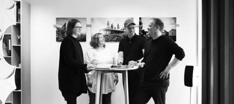 "Black-white photo of the people behind ""Tanken arkitektur"", in their studio with some of the designs illustrated behind them."