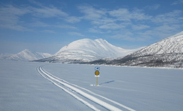 Snowmobile track with a speed sign next to it, in the middle of an open, white landscape surrounded by majestic mountains.