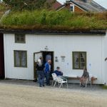 People going in and out of a small white wooden house with grass on the roof, the Gunvor House at Lapphella.