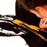 A child drawing a mysterious man dressed in black and orange.