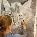 Young girl drawing a grey cat on a big canvas.