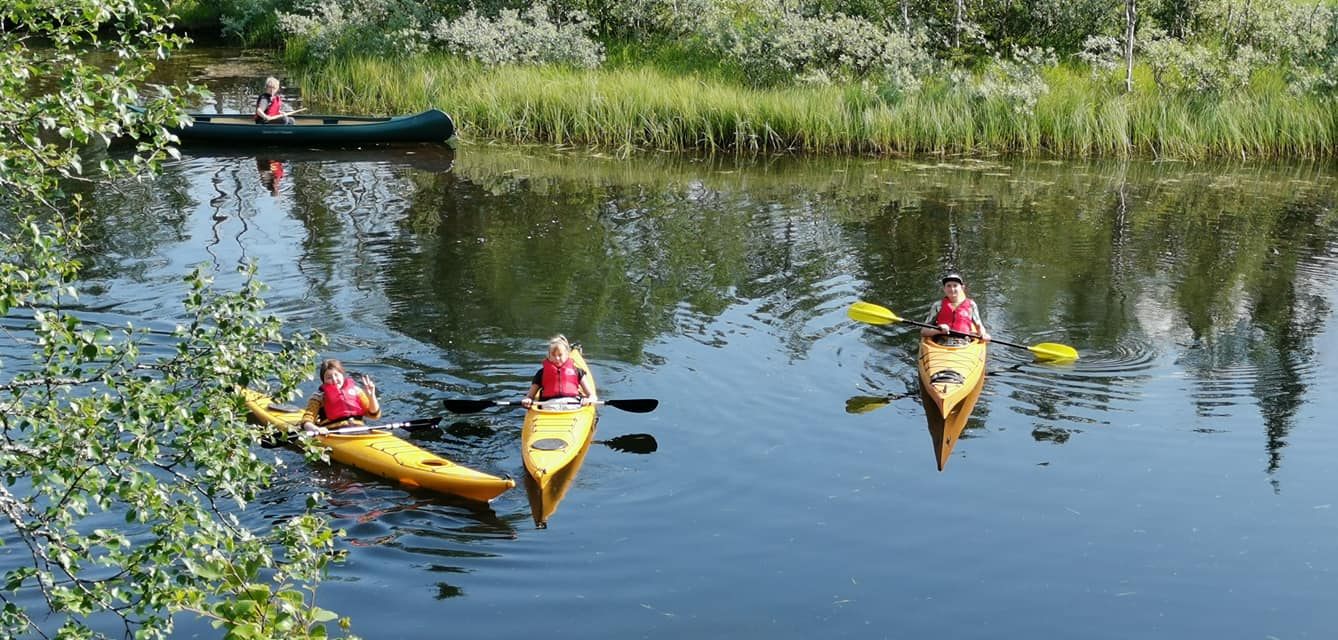 Several kids kayaking in yellow kayaks and red life vests, in Bleikvasslia during a mountain camp arranged for children.