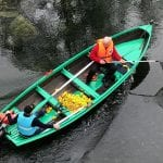Duck race on the Røssåga river with two people sitting in a green boat trying to collect small floating ducks in the water.