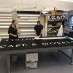 Workers at Hasvo, foliation and printing a sign for a local company, at their workshop.