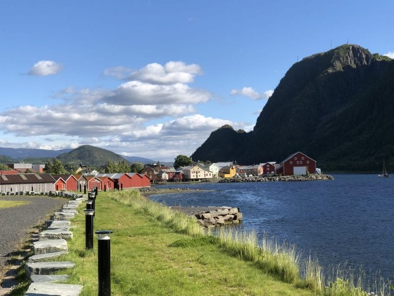 Colorful houses next to the fjord in Mosjøen with the tall mountain, Øyfjellet in the background on a sunny summer day.