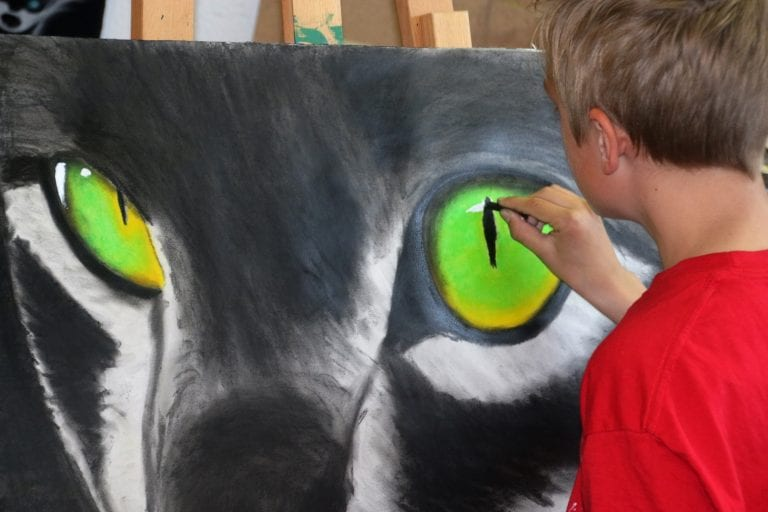 Young boy in red drawing the green powerful eyes of a wolf he is making on a big canvas.