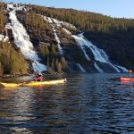 Two people kayaking in front of two big waterfalls in the green mountains behind them.