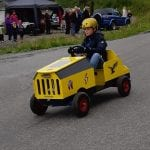 Young boy with a yellow helmet driving a small home-made yellow car down the road with people watching him.