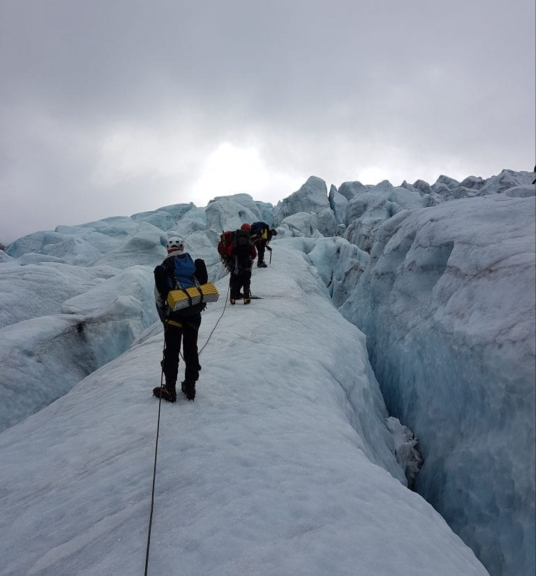 People climbing a steep glacier filled with crevasses, together with ropes between each other.