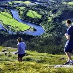 Two people walking down a green mountain with a view over the forest and the river, Røssåga, in a U-formation.