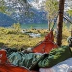 Person relaxing in a green sleeping bag in the orange hammock hanging between trees with a great fjord and mountain view.