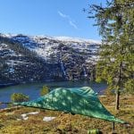 Tent hanging between two trees above the ground, with a great view of the fjord and white mountains.