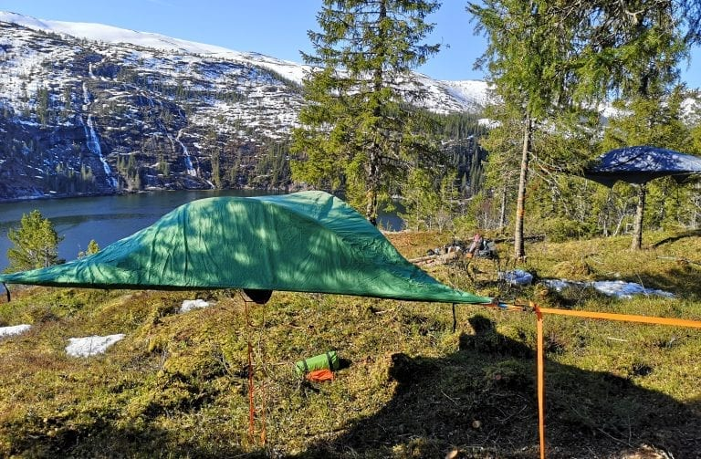 Tent hanging between trees above the ground, with a great view of the fjord and white mountains.