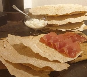 Flat bread served with dried meat and sour cream.