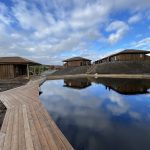 Outdoor pool and sauna in front of wooden cabins.
