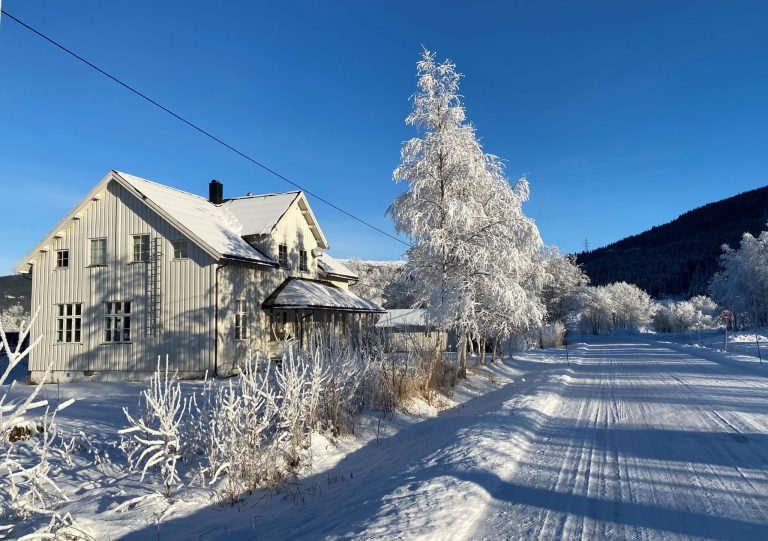Old white wooden house in snowcovered landscape and bright sun